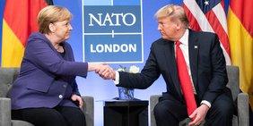 Donald Trulmp und Angela Merkel sitzen leicht schräg versetzt nebeneinander in Sesseln und reichen sich die Hand.