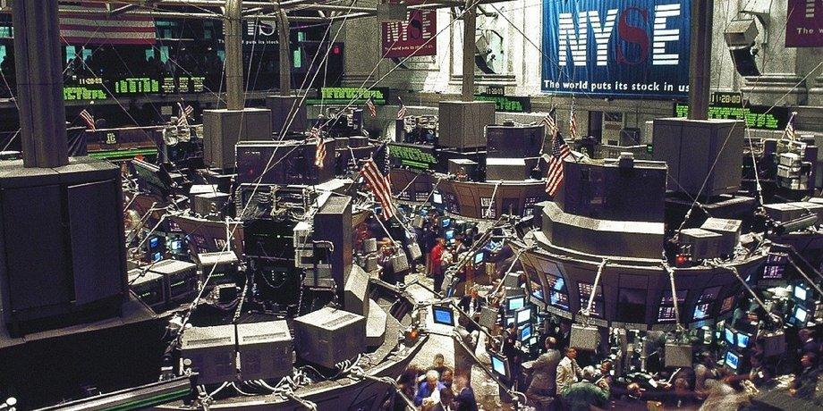 Blick in die Börse von New York von oben. Auf dem Parkett sind viele Menschen unterwegs, über ihnen hängen Monitore und an der Wand in großen Buchstaben: NYSE.