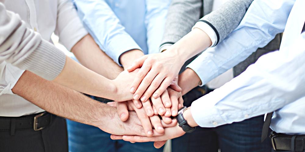 Eine Gruppe von Menschen legt die Hände in der Mitte übereinander.