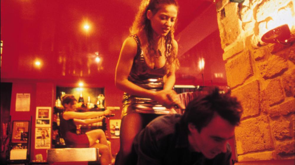 """Szene aus dem Film """"Baise-moi"""" mit zwei Frauen, die einen auf dem Boden knieenden Mann mit Pistolen bedrohen."""