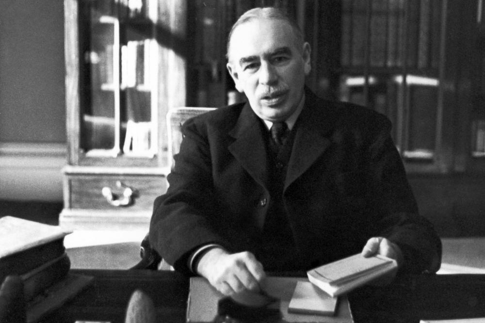 John Maynard Keynes am Schreibtisch mit einem Buch in der linken Hand. Bild in Schwarzweiß.