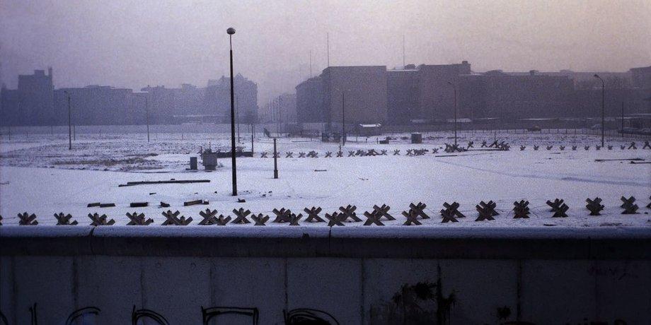 Blick über die Berliner Mauer auf den Potsdamer Platz, der schneebedeckt und ohne Gebäude drumherum ist. Foto in Schwarzweiß von 1979.