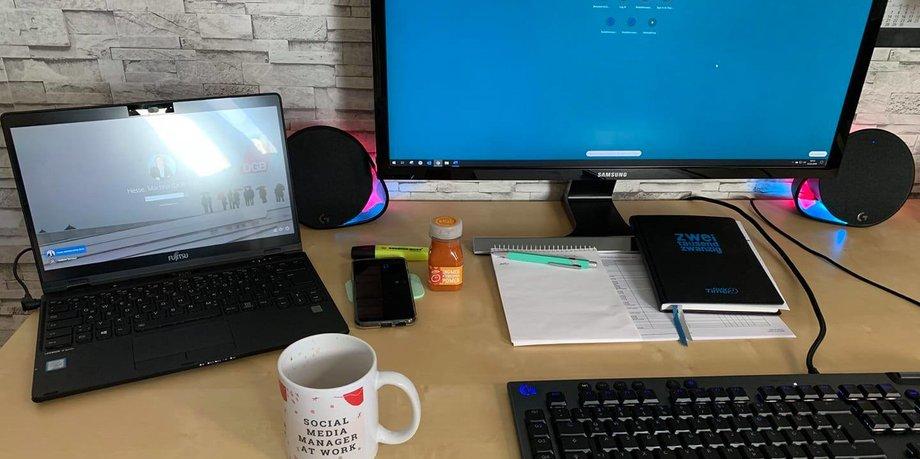 Schreibtisch mit Computer und Laptop, Taschenkalender und Schreibutensilien, Kaffeetasse und Handy.