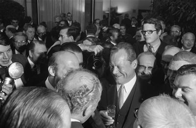 Willy Brandt in einer Gruppe von Menschen mit einem Sektglas in der Hand.