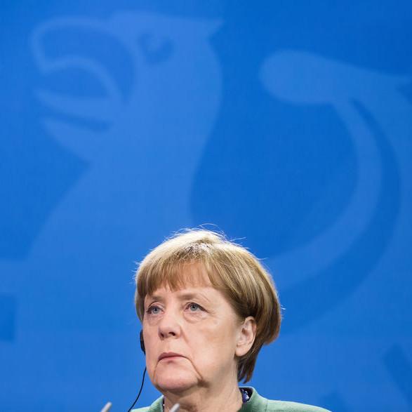 Angela Merkel, von der der nur der Kopf zu sehen ist, steht vor einer blauen Wand, auf der schemenhaft der Bundesadler zu erkennen ist.
