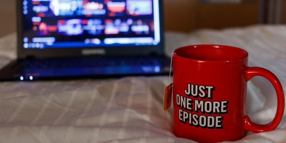 """Rote Kaffeetasse mit der Aufschrift """"Just One More Episode"""" steht auf einem Bett vor einem Laptop."""