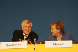 Angela Merkel und Horst Seehofer sitzen nebeneinander auf einem Podium.