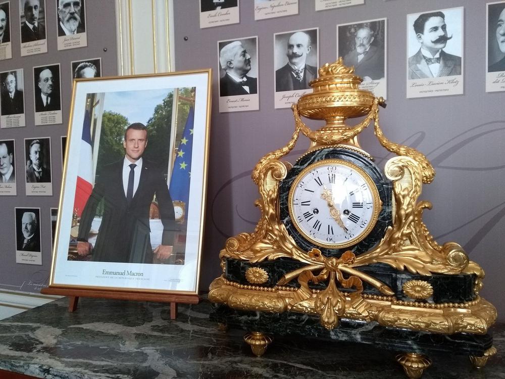 Offizielles Foto von Emmanuel Macron im Bilderrahmen neben einer goldenen Kaminuhr im Empire-Stil.