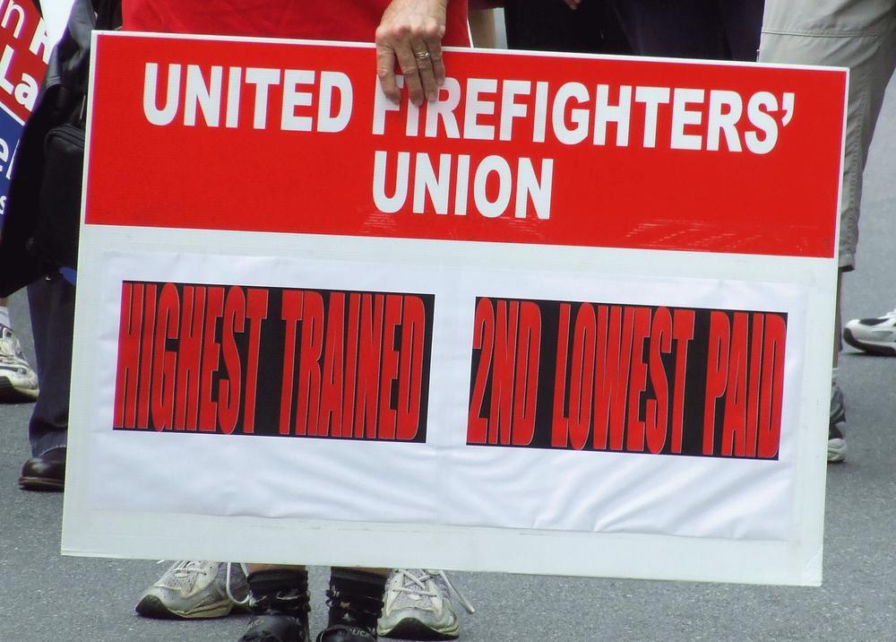 Ein Plakat der Feuerwehr-Gewerkschaft mit der Aufschrift (übersetzt): Am besten ausgebildet, am zweitschlechtesten bezahlt.