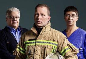 Ein Feuerwehrmann in der Mitte, rechts neben ihm ein Busfahrer, links eine Krankenschwester - alle in Dienstkleidung blicken ernst in die Kamera.