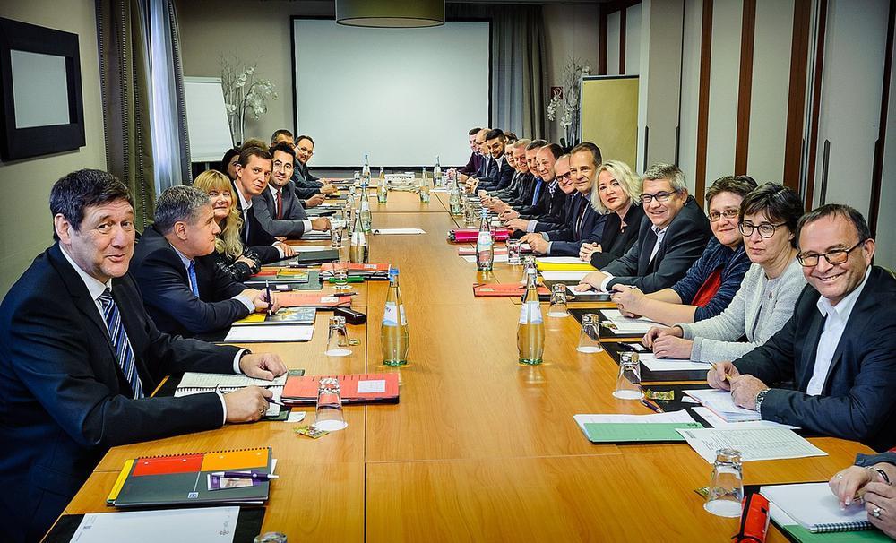 An einem langen Holztisch sitzen rechts und links die Vertreter von Gewerkschaften und Unternehmern.