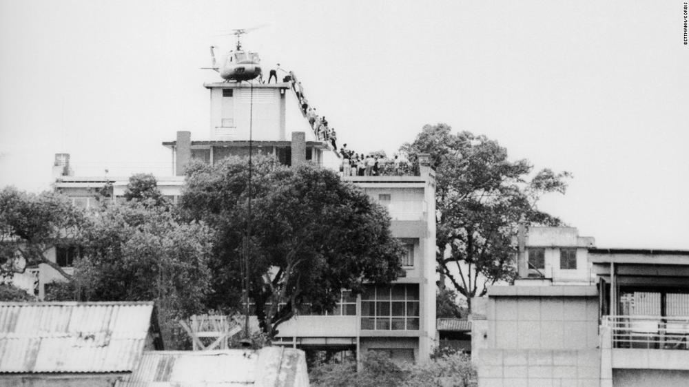 Auf dem Dach eines Hauses steht ein Hubschrauber, zu dem eine Schlange von Menschen über eine Leiter gelangen will.