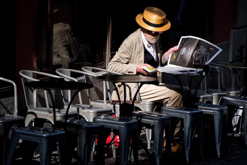Ein Mann mit Strohhut sitzt an einem Tisch in einem Straßencafé und liest Zeitung.