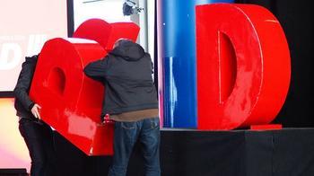 Arbeiter bauen eine Bühne ab und tragen den großen Plastikbuchstaben P von SPD weg.