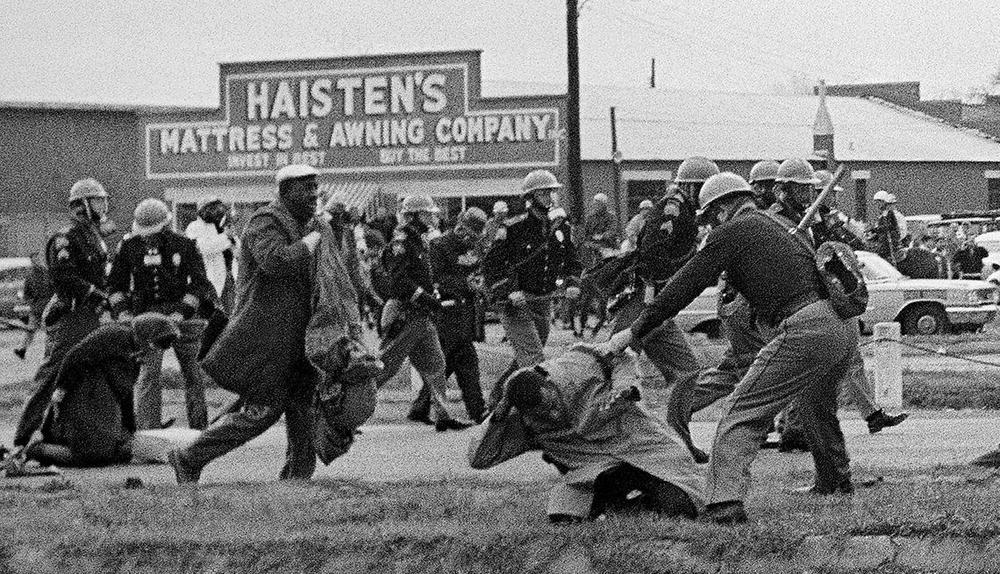 Schwarzweißbild von Polizisten, die mit Knüppeln gegen Demonstranten vorgehen.