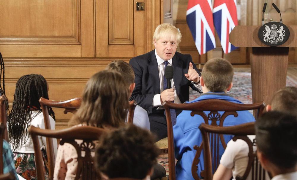 Boris Johnson sitzt vorne und erklärt Kindern seine Politik.