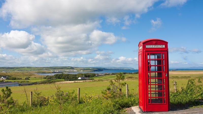 Rote englische Telefonzelle vor einer grünen irischen Landschaft.