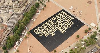 """Riesenplakat auf einem Platz in Genf liegend. Der Text: """"What would you do if your income were taken care of?"""""""