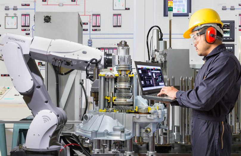 Ein Mann in blauer Arbeitskleidung hält einen Labtop und steht vor einem Industrieroboter.