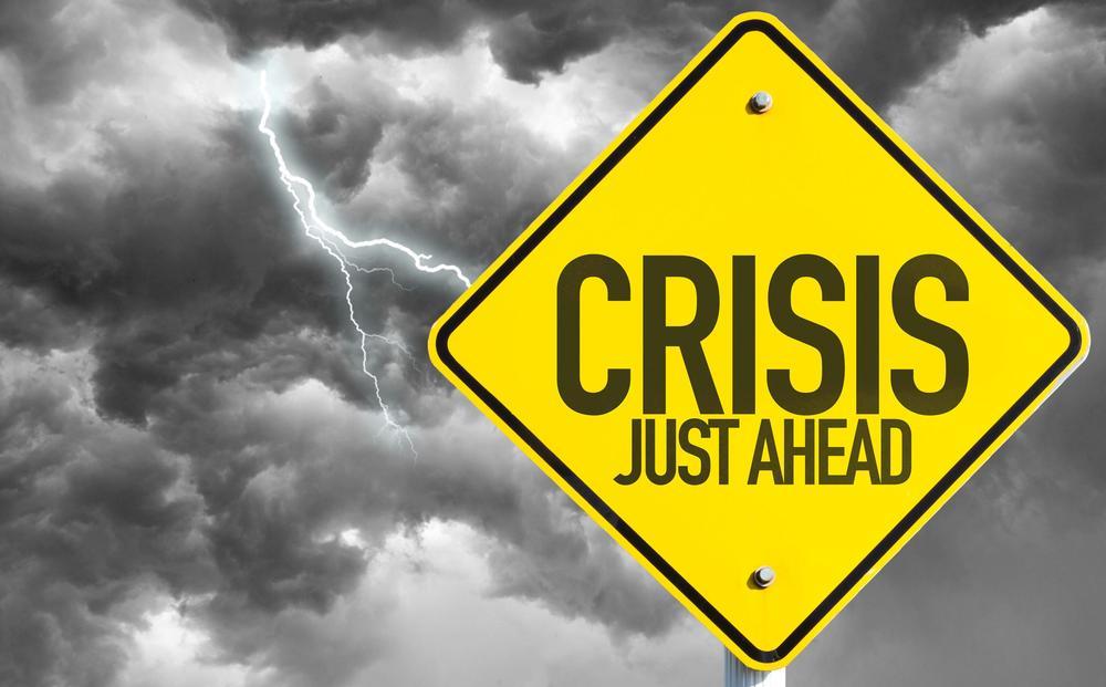 """Gelbes Warnschild mit der Aufschrift """"Crisis ahead"""" vor dunkelgrauen Wolken."""