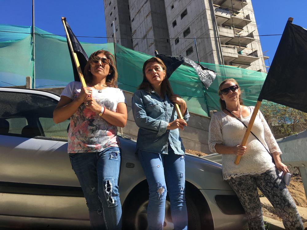 Drei Frauen mit schwarzen Fahnen protestieren vor einem Hochhausrohbau gegen Immobilienspekulation.
