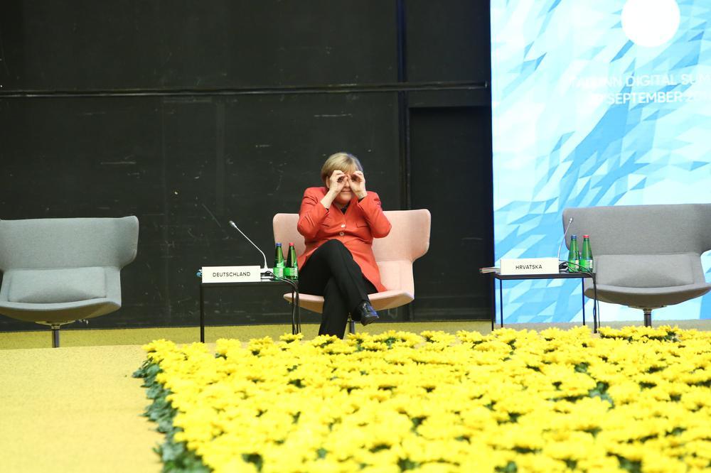 Angela Merkel sitzt in einem großen Raum allein im Hintergrund auf einem Sessel und blickt durch ihre Hände, die sie wie ein Fernglas geformt hat. Vor ihr erstreckt sich eine Wiese aus künstlichen gelben Blumen.