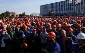 Eine große Menge von Arbeitern protestiert vor einer Fabrik. Fast alle tragen Blaumann und rote Helme.