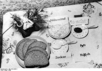 Tagesration eines Normalverbrauchers an Essen auf einem Tisch: drei Scheiben Brot, etwas Haferflocken, Zucker und Marmelade