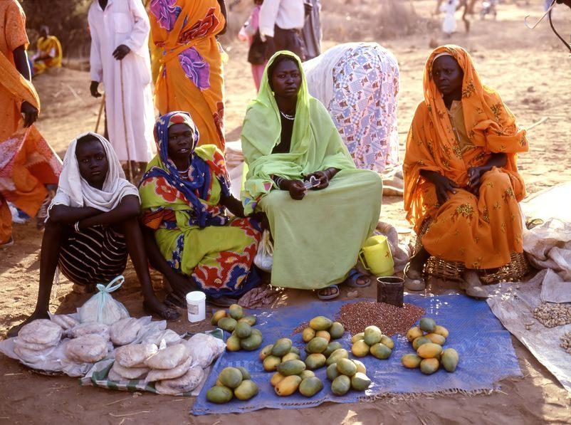 Dunkelhäutige Frauen in bunten Gewändern sitzen auf einem Tuch, auf dem sie Papaya anbieten.