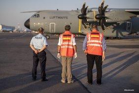 Drei Männer mit orangen Westen, auf denen die deutsche Flagge und das Wort Germany pragen, stehen auf einem Flugfeld und beobachen mit dem Rücken zur Kamera ein Flugzeug.