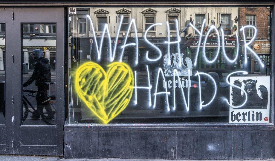 Bild von einem leeren Schaufenster, auf dem steht: Wash your hands. Dahinter klebt ein Plakat mit einem Bären, auf dem Berlin steht.