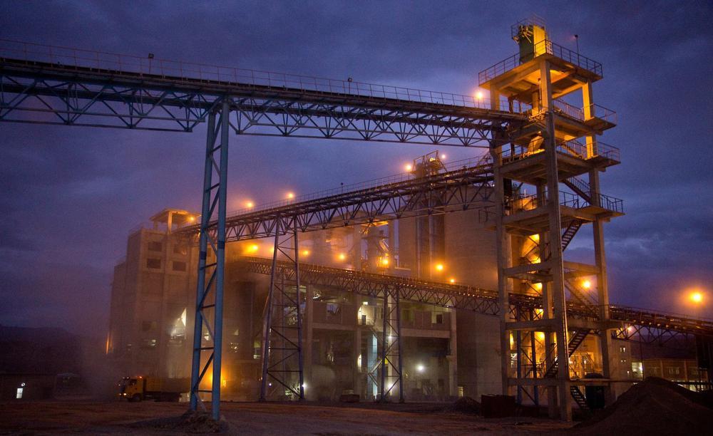 Zementfabrik bei Nacht, im Staub, mit gelben Scheinwerfen, vor dunkelblauem bewölktem Himmel.