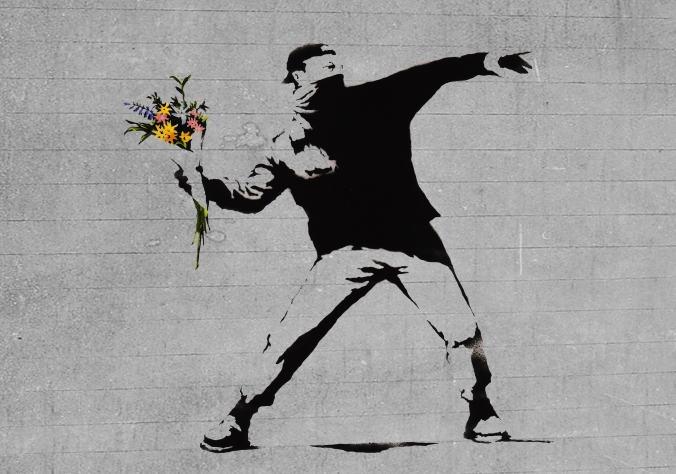 Wandgemälde von Banksy mit einem Autonomen, der dazu ansetzt einen Strauß Blumen zu werfen.