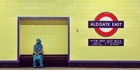 Eine Frau mit Kleid und Kopftuch in Türkis sitzt auf einer Bank in der U-Bahn-Station Aldgate in London vor einer gelb gekachelten Wand.