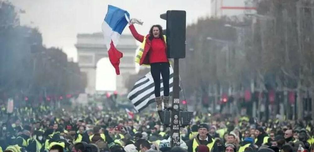 Demonatration der Gelbwesten in Paris mit einer Frau auf einer Ampel, die die französische Flagge schwenkt.