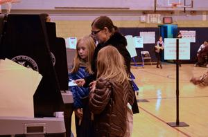 Wahllokal in New York, wo eine Mutter in Begleitung ihrer Töchter ihre Stimme abgibt.