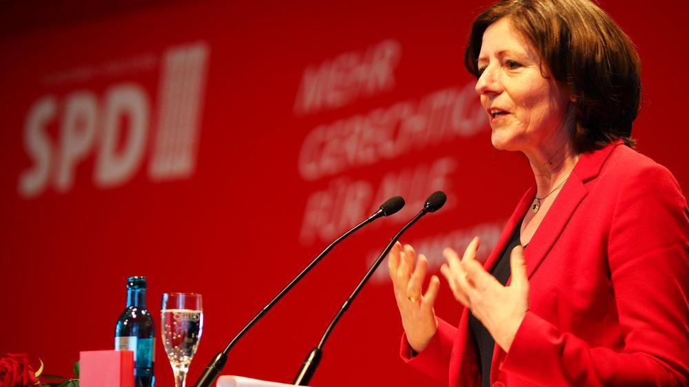 Malu Dreyer bei einer Rede vor rotem Hintergrund.