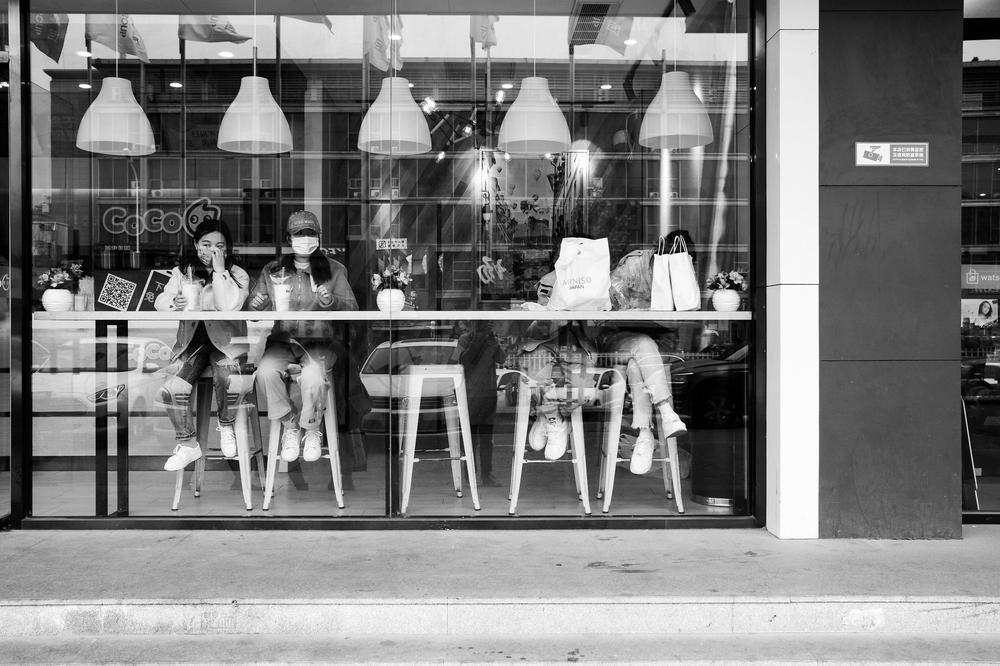 Blick durch ein Schaufenster in ein Imbissrestaurant, in dem Menschen an einem Stehtisch stehen und nach draußen blicken. Sie tragen Atemschutzmasken.