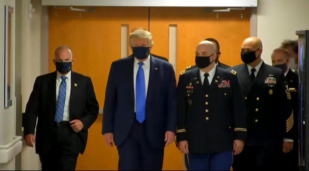 Donald Trump geht begleitet Militärs und Sicherheitsleuten einen Flur entlang auf die Kamera zu, die das Bild aufnimmt.