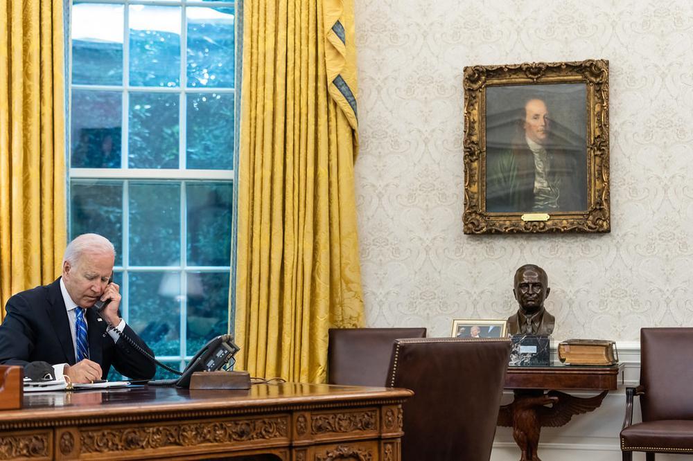 Ein Mann, Joe Biden, sitzt an seinem Schreibtisch im Oval Office und telefoniert.