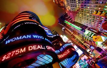 Times Square in New York bei Nacht mit Börsenmeldungen.