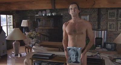 """Szene aus dem Film """"Ein Fisch namens Wanda"""", bei der John Cleese nackt dasteht und sich ein gerahmtes Bild einer Frau vor seinen Intimbereich hält."""