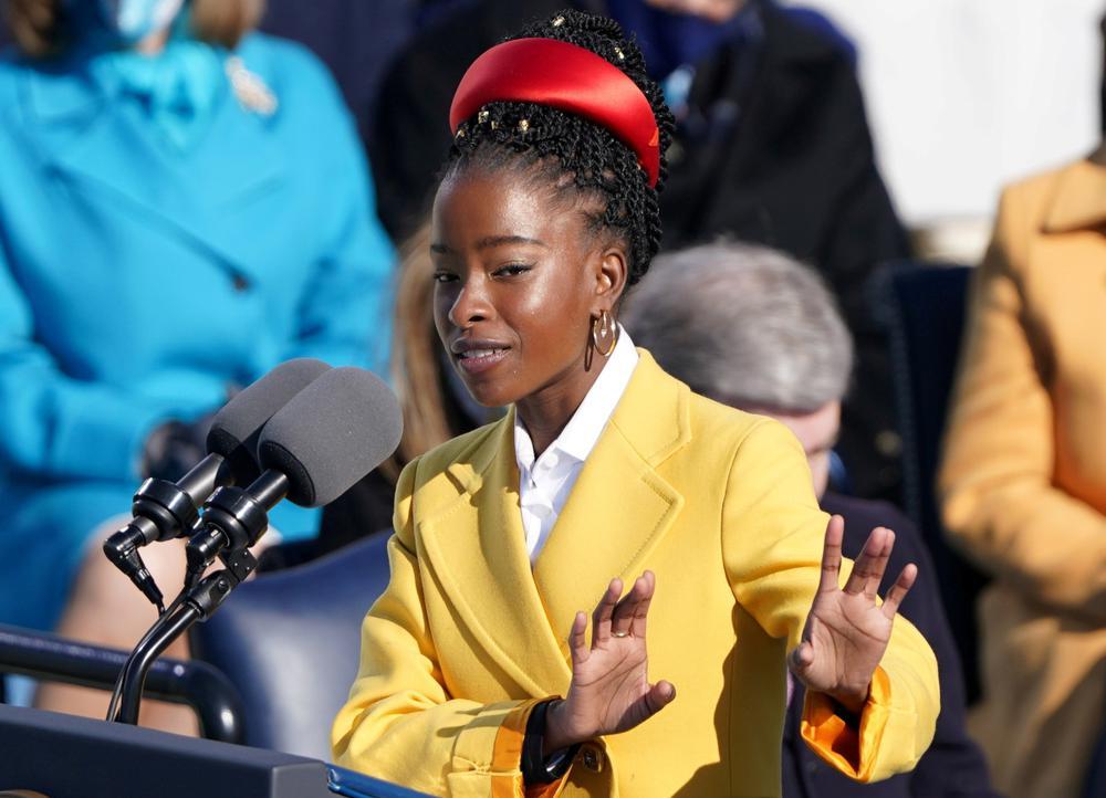 Die junge Schwarze Amanda Gorman spricht in zwei Mikrophone vor sich. Sie trägt einen langen gelben Mantel und einen dicken roten Haarreif.