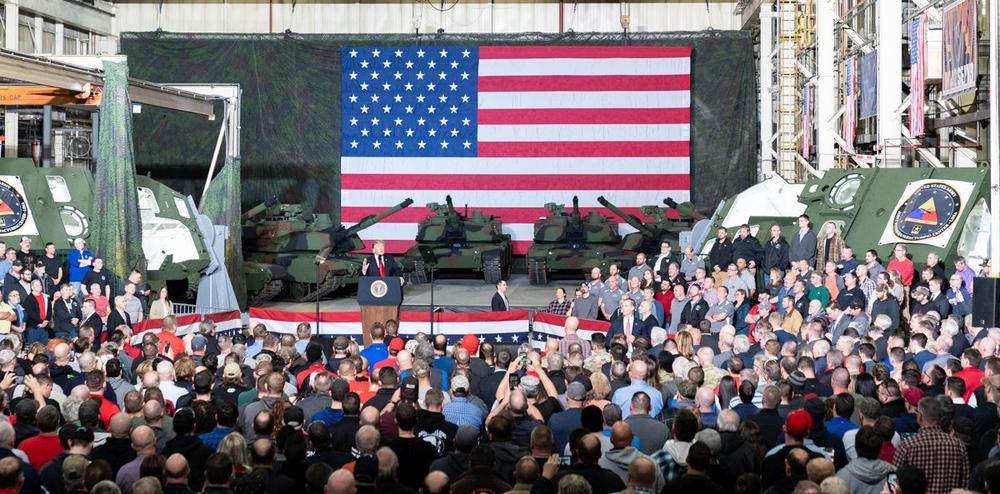Donald Trump bei einer Rede vor einer großen US-Flagge und Panzern.