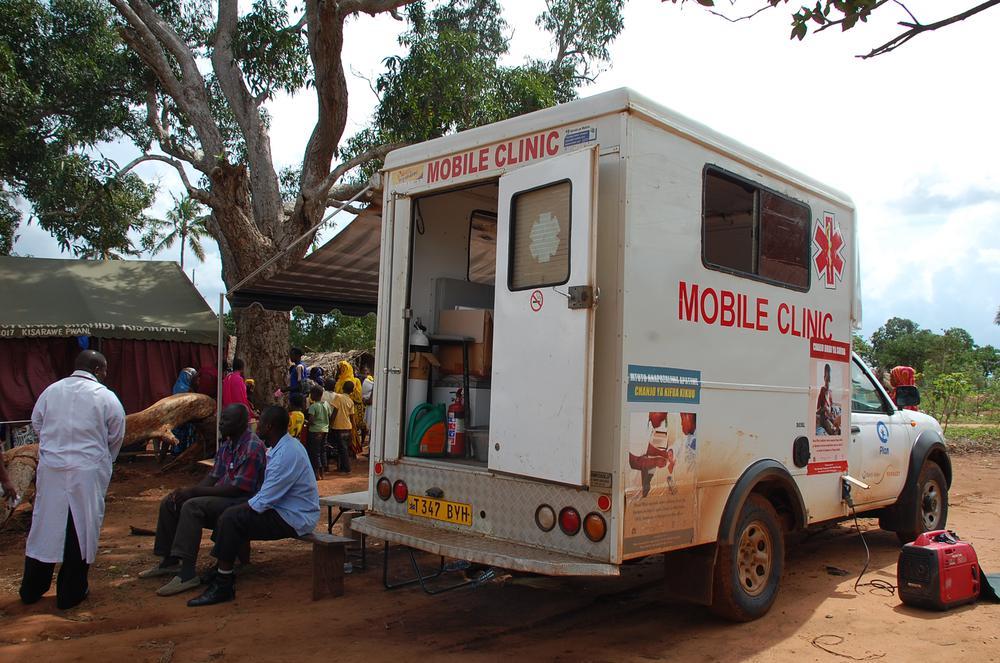 Patienten warten vor einem Transporter, der eine kleine Klinik enthält.