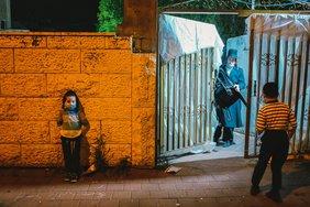 Nächtliche Szene in Israel, bei der ein orthodoxer Jude mit Schläfenlocken ein stählernes Tor öffnet, vor dem zwei Jungen stehen. Alle tragen Gesichtsmasken.