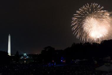 Nachtaufnahme von Washington D.C. mit angestrahltem Obelisk und einem Feuerwerk.
