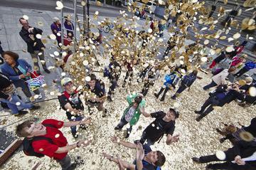 Geld fällt von oben auf eine Menschenmenge