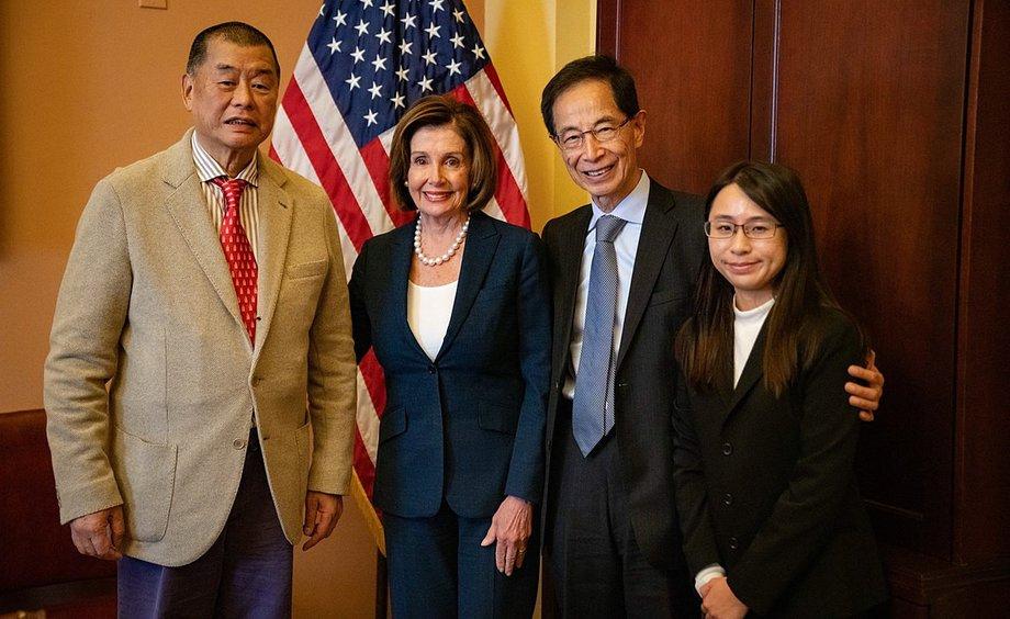 Nancy Pelosi steht vor einer US-Flagge zwischen zwei chinesischen Männern, links daneben eine Chinesin.