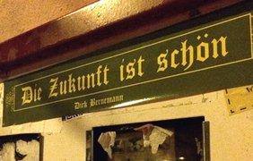 Ein grünes Schild an einer Wand, auf dem steht: Die Zukunft ist schön. Darum sind Reste von Plakaten zu erkennen.